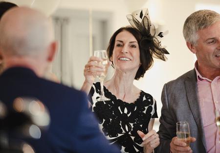 Os pais da noiva estão brindando com a filha e o genro no dia do casamento. Eles estão levantando seus copos de champanhe. Foto de archivo