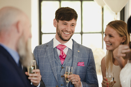 Groom is socialising with guests on his wedding day while they dirnk champagne.