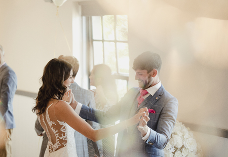 Bruid en bruidegom genieten van het dansen samen op hun trouwdag.