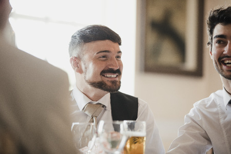 Close up shot of a best man at a wedding, socialising with the guests at the reception.  Stock Photo