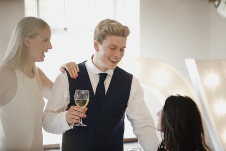 若いカップルは、彼らが出席している結婚式で他のゲストと交流しています。彼らはシャンパンを飲み、レセプションに座っている先輩の女性と話