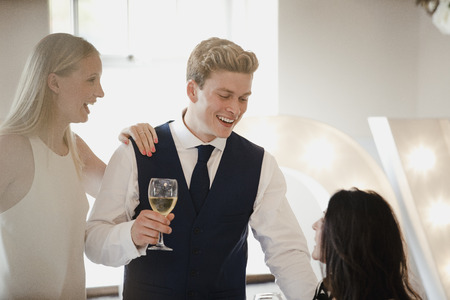 Young couple are socialising with other guests at a wedding they are attending. They are drinking champagne and talking to a senior woman who is sitting down at the reception. Stok Fotoğraf