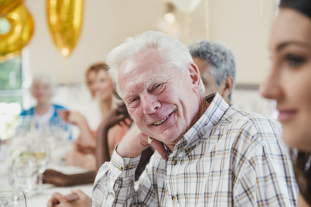 Happy senior man at a birthday party with his friends and family. He is sitting at the table smiling for the camera with his head resting on his hand.  Stock fotó