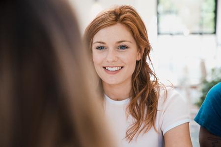 若い女性は誕生日パーティーで社交をしている。赤毛の女性がカメラに背中を向けた人と話している。