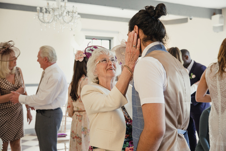 Senior woman is appreciating her grandson on his wedding day. She is dancing and talking to him with her hands on his face.