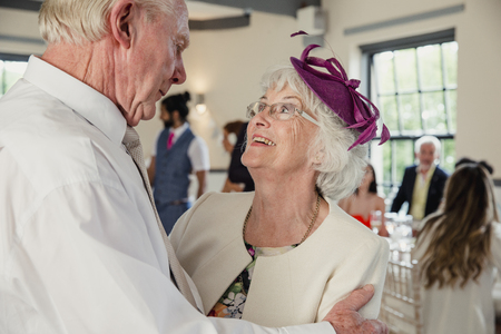 Senior couple are sharing a dance at a wedding. They are looking lovingly at each other while they dance.