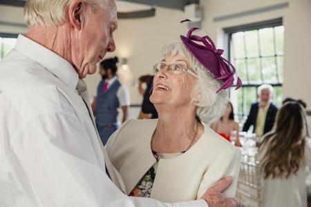 Senior paar delen een dans op een bruiloft. Ze kijken elkaar liefdevol aan terwijl ze dansen.