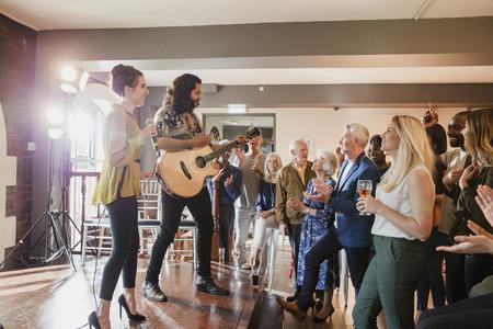 結婚式のゲストは、いくつかのアコースティックエンターテイメントを楽しんでいます。ギターを弾いている男と歌う女性がいて、みんなが一緒に 写真素材