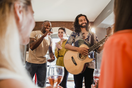 Two young men and a young woman are singing and playing guitar at an entertainment venue to a crowd.  Reklamní fotografie