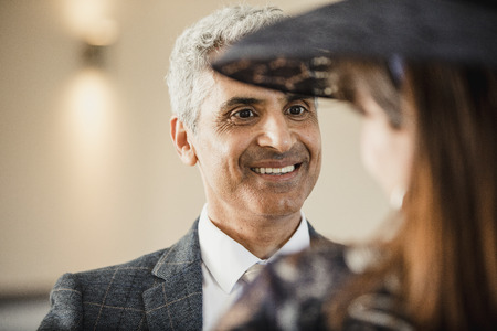 Mature man is having a conversation with his wife at their son's wedding. She has her back to the camera and is wearing a fascinator.