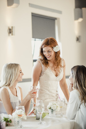 Beautiful bride is socialising with some of her friends who are guests at her wedding. They are sat at a table, drinking wine as they talk.