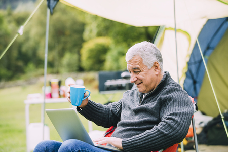 Senior man is relaxing in a chair by his tent in the campsite. He is enjoying a cup of tea while using a laptop. Stock Photo