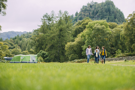 Three generation family have left their tent to go for a hike with their pet dog. There is a grandmother, a mother and her two children.  Stock Photo
