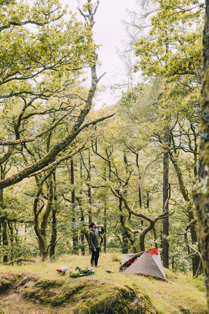 Young man is wild camping alone in the woodlands of the Lake District. He is standing outside of his tent, having a drink from a flask. Banco de Imagens