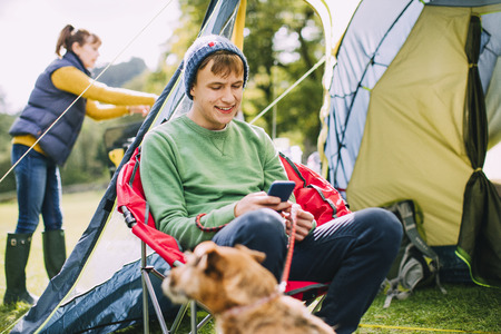 Teenage boy is sitting in a camping chair by his tent, engrossed in his smart phone while his Mum puts up the tent.