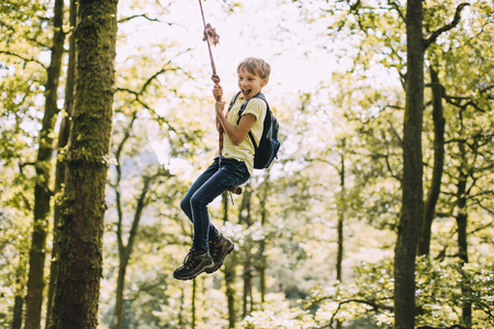 Little boy is having a go on a rope swing he has found while hiking.