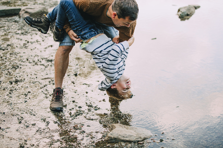 Little boy and his father have been hiking and found a pond. His father is holding the boy upside down, teasing to dunk him in the water.
