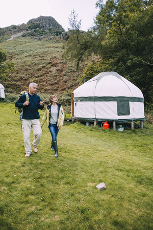 Senior couple are leaving the yurt they have been camping in to go for a hike around the Lake District.