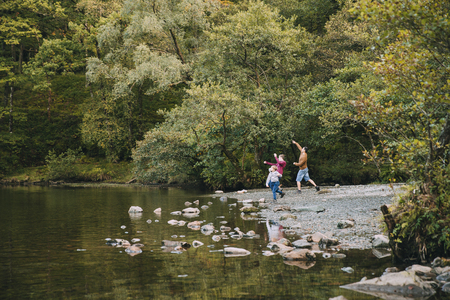 Two boys are skimming stones in a lake with their father.