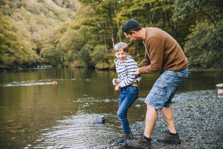 Little boy and his father have been hiking and found a pond. His father is holding the boy, teasing to throw him in the water.  Stock Photo