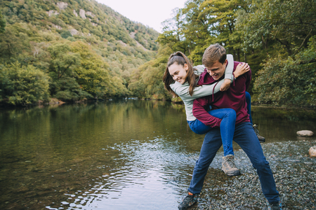 Teenage boy has his sister in a piggy back hold and is pretending to throw her in to a lake while they are out hiking.  版權商用圖片