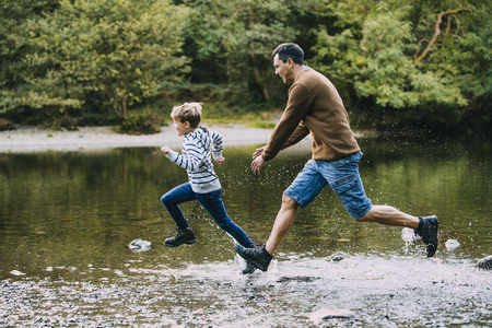 Little boy is being chased in to the lake by his father while they are out hiking.  Banco de Imagens
