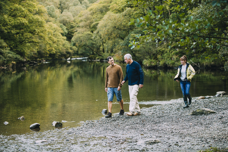 Mid adult man is enjoying a walk around the Lake District with his parents. He is walking with his father and his mother is just behind them.