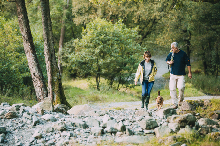 Senior couple are hiking through the Lake District together with their pet dog. Stok Fotoğraf - 100483019