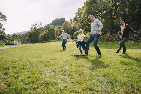 Three generation family are playing football together in a field. There are two boys, their father and their grandfather. Stockfoto