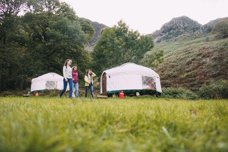 3世代の家族は、一緒に長いハイキングの後、彼らのキャンプのユルトに戻っています。 写真素材