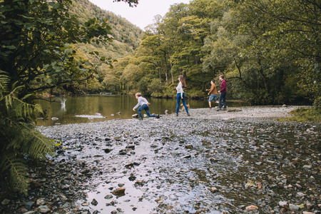 Family are skimming stones on a lake in the Lake District. Stok Fotoğraf