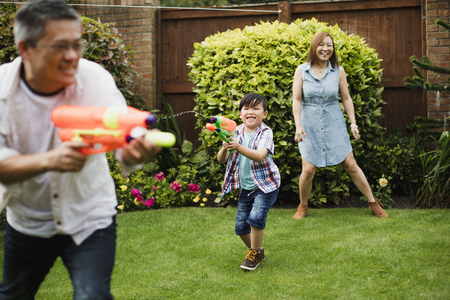 Family are having a water fight in the garden with pistols.  Stock fotó