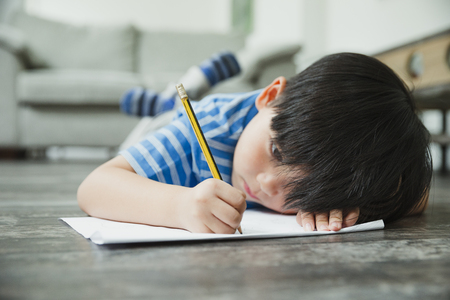 Little boy is lying on the floor, concentrating on his homework.