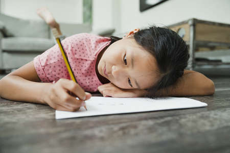 Little girl is lying on the floor in the living room, concentrating on her homework. Stock Photo
