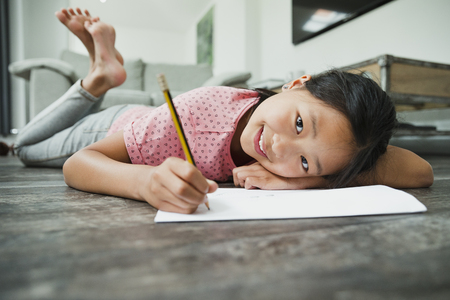 Little girl is smiling for the camera while lying on the floor doing her homework.