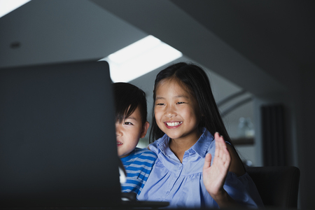 Little girl and her younger brother are using the laptop to video call their family. They are happily waving to the laptop.