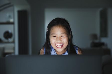 小さな女の子は、中国で彼女の家族をビデオ通話するために夜にラップトップを使用しています。
