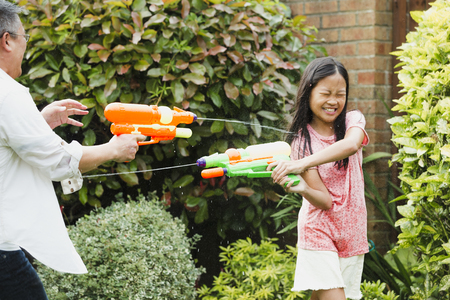 Little girl and her father are having a water fight in the garden with water pistols. The little girl is getting soaked and has her eyes closed as she tries to shoot back.