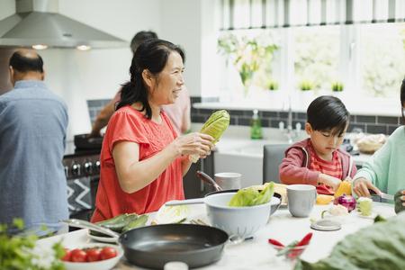 Tiro de una mujer mayor que prepara verduras para un salteado con su familia en la cocina. Ella está sosteniendo lechuga mientras habla.