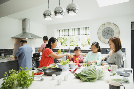 Three generation family are preparing vegetables for a stir fry in the kitchen of their home together. 스톡 콘텐츠 - 97593368