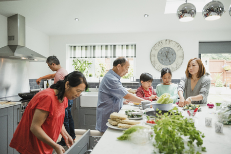 3 세대 가족이 함께 집 부엌에서 볶음 요리를 위해 야채를 준비하고 있습니다.
