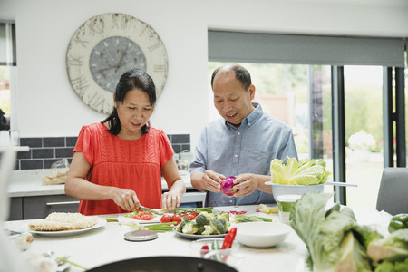 Senior couple are preparing vegetables together in the kitchen to make a stir fry. Stock Photo