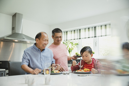 Family are in the kitchen eating a homemade stir fry together. The little boy is sitting with his food and his dad and granddad are standing.