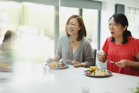 Family are enjoying eating a stir fry dinner together at home. There is a senior woman and her daughter in the shot and theyre both laughing across the table to someone out of the frame. Stock Photo