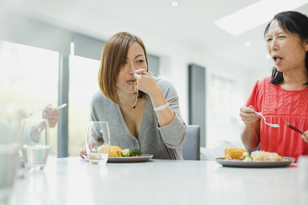 Two women are sitting with their family enjoying a stir fry dinner at home. The mature woman has a mouthful of noodles and the senior woman is laughing. Stock Photo - 97532030