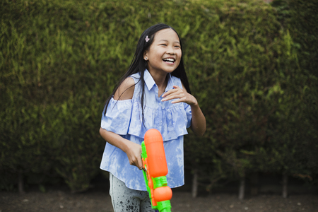Little girl is having a water fight in the garden with her family. She is laughing with a water pistol in her hand.