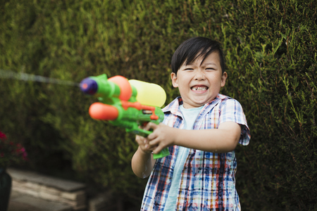 Little boy is having a water fight in the garden with his family. He is making a face as he gets hit with a water pistol in his hand.