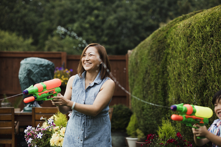 Family are having a water fight in heir garden with water pistols. The mother and her son can be seen in shot, aiming at people out of the frame.