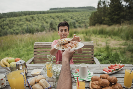 Point of view angle of mixed race boy getting handed a plate of hot cross buns. Stock Photo - 97663710
