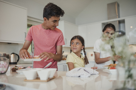 Siblings preparing food in the kitchen. Stock Photo